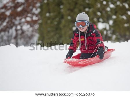 A young boy shows his excitement sledding down a hill in winter.