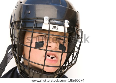 A young boy shows off his missing teeth while in his hockey gear. - stock photo