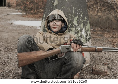 a young boy sits near the warhead. boy sitting on the ground. front part of the rocket. wandering boy. boy with a gun. Post apocalypse.  traveling on foot in a post-apocalyptic world.