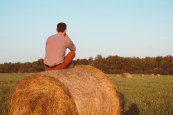 A Young boy sits on a hay bale and enjoys living happy on the country