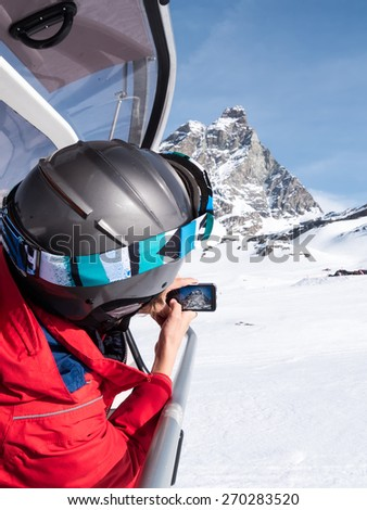 A young boy, sitting on a chairlift, takes a photo of the Matterhorn using his smartphone. Winter season, sunny day. western european Alps, Valle d'Aosta, Italy, Europe.