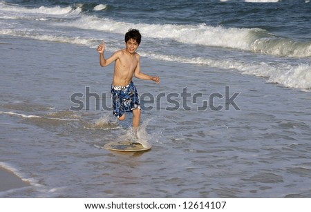 A young boy skimboarding.