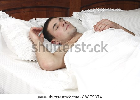 a young boy sleeps in a bed on the white sheet