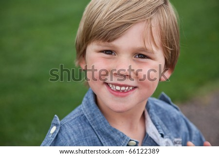 A young boy smiling in the park.