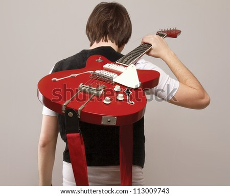 A young boy standing with his back with bass guitar on grey background
