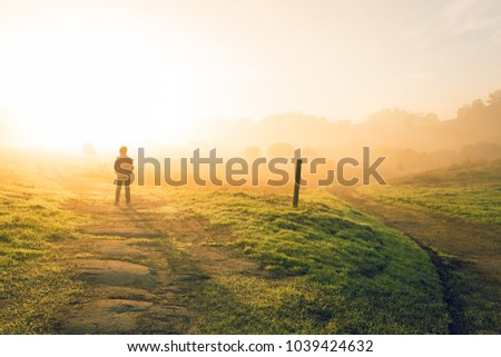 A young boy stands at the edge of a road less traveled, watching the sun rise through fog in the wilds of northern California.