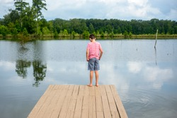 A young boy stands on a wooden fishing pier that sits on a freshwater bass pond and looks down toward the water on a hot summer day in July located in Louisiana.