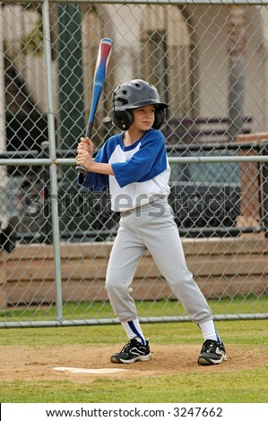 A young boy up to bat in a baseball game