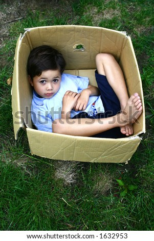 A young boy using a cardboard box as a place to hide . Concept : Expand and grow