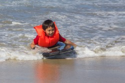 A young boy wearing a life jacket rides a boogie board laying on his stomach to the shoreline of a beach.