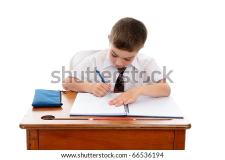 A young boy wearing a school uniform sitting at desk writing in a book.  White background.