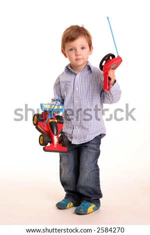 A young boy with a remote controlled car isolated on a white background