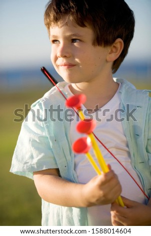 A young boy with a toy bow and arrows