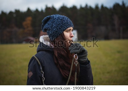 A young breeder in winter clothes blows a dog whistle to summon a stray dog. Authentic people. Binary portrait of girls aged 20-24 whistling at Barbu tcheque, Czech hunting breed. Foto stock ©
