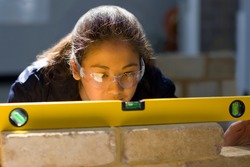 A young Bricklaying student in a vocational school using the spirit level on a brick wall while closely watching the alignment of the bricks