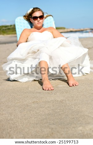A young bride wearing her wedding gown while sunning on the beach