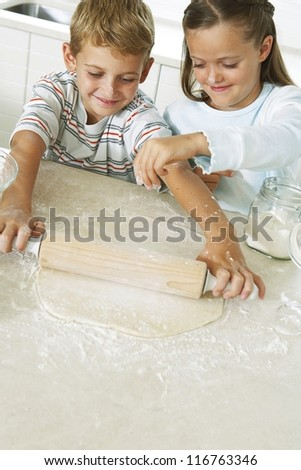 A young brother and sister enjoying themselves in the kitchen playing at being pastry chefs as they roll out the dough