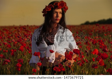 A young brunette girl in a white shirt stands in a poppy wreath in a poppy field and looks away. Fine art portrait.