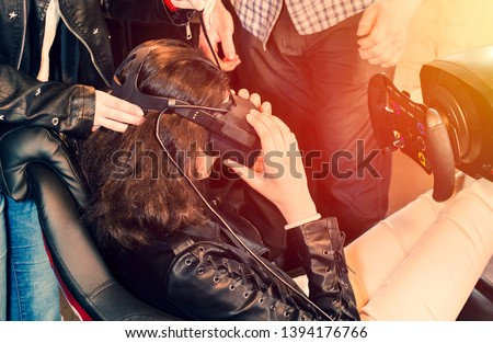 A young brunette girl is helped to wear VR glasses.Gamer plays VR race on a gaming club. Virtual reality on car simulator.Female teenager is sitting behind a car simulator and preparing to play games.