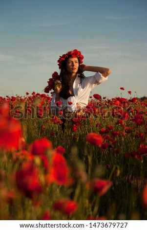 A young brunette girl is standing in a poppy field, putting a bouquet of poppies on her shoulder with one hand, raising her other hand to her head, looking into the distance. Fine art portrait
