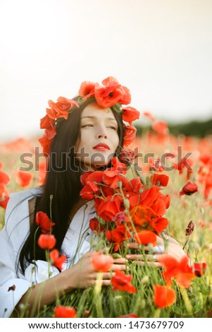 A young brunette girl sits in a poppy field and leans a bale of poppies to her face, looks into the distance. Fine art portrait