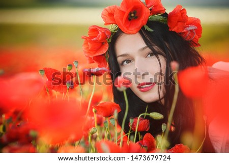 A young brunette girl sits in a poppy field at the flower level and looks at the camera half-turn. Fine art portrait.