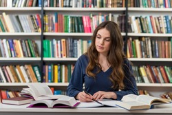 A young brunette girl who is sitting at a desk in the library with an open note book writing out information from many opened books around her, looking at a book, a concept of studying and research