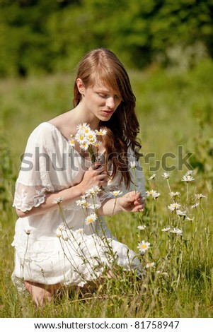 A young, brunette lady picks flowers on a summer meadow