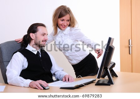 A young business man and a girl running on the computer in the office. - stock photo