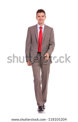 A young business man is walking. He is smiling and looking to the camera. isolated over white background