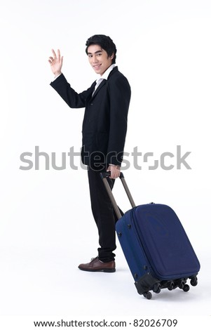 A young business man pulling luggage and waving hand