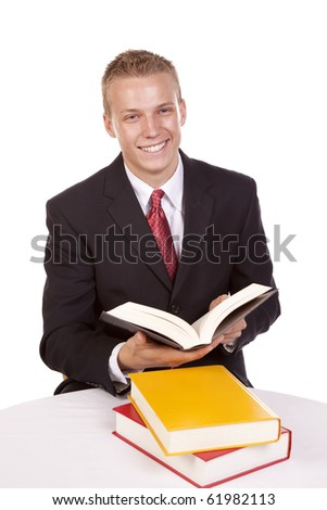 A young business man sitting at a table with a stack of books reading and showing a happy expression. - stock photo
