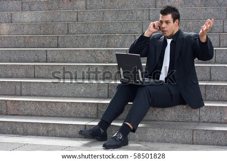 a young business man sitting on steps looking upset speaking on the phone with a laptop in front of him