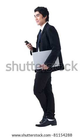 A young business man standing with laptop and phone