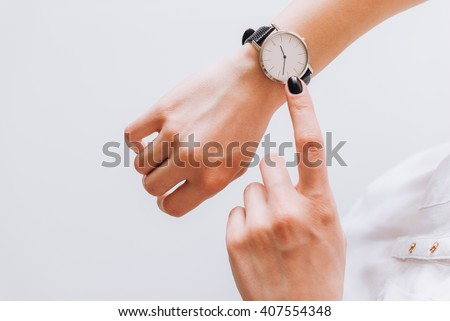 A young business woman is late on time, she shows the deadline on her classic watch