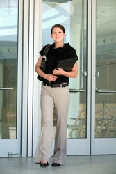 A young business woman walking out of office building
