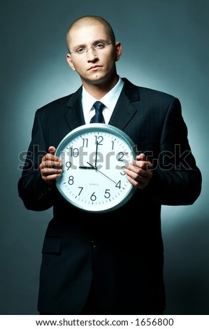 A Young businessman checking his watch. Time is money