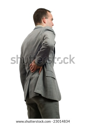 A young businessman holding his back in pain, isolated against a white background