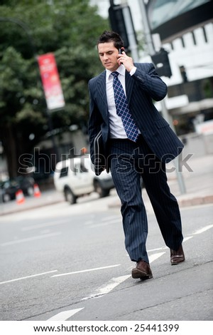 A young businessman in a suit holding mobile phone whilst crossing road