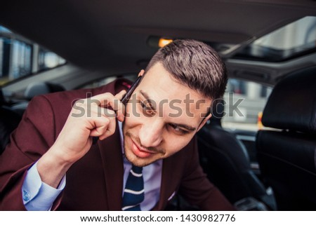 A young businessman is looking through a window in his stretch limo and smiling