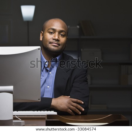 A young businessman is seated at a desk and is working on a computer.  He is looking at the camera.  Square framed shot.