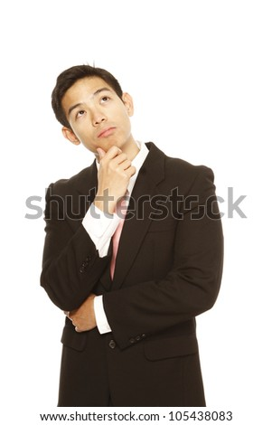 A young businessman looking up and thinking