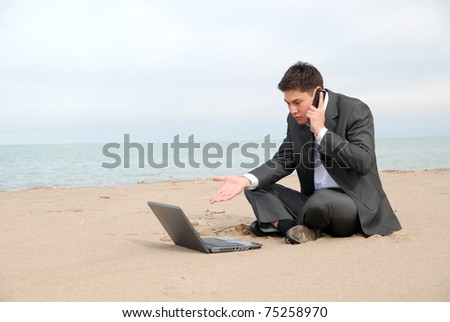 A young businessman sitting c in front of a laptop and talking on a mobile phone.