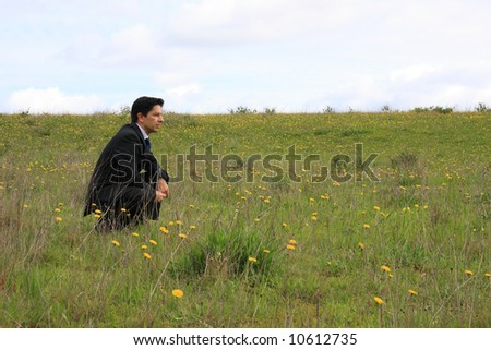 A young businessman sitting in a field thinking about a solution