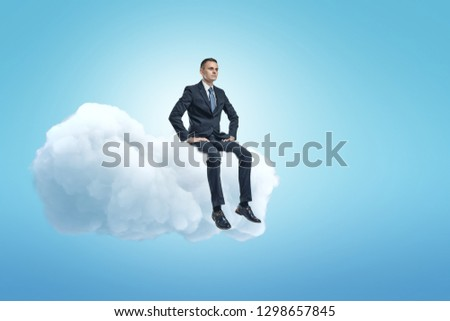 A young businessman sitting on a white fluffy cloud in the blue sky with lots of copy space left. Dream big. Business and strategy. Forethought and vision.