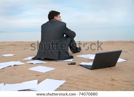 A young businessman sitting on the beach. Around it are scattered documents. - stock photo