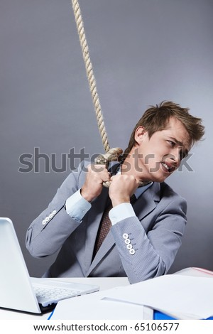 A young businessman tightens the noose on his neck