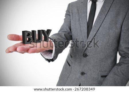 a young businessman wearing a gray suit shows the word buy, three-dimensional, in the palm of his hand