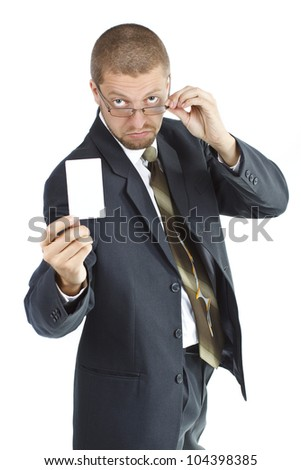 A young businessman wearing suit and tie is holding a blank card in his right hand, touching his glasses with his left hand and looking from behind his glasses - isolated on white