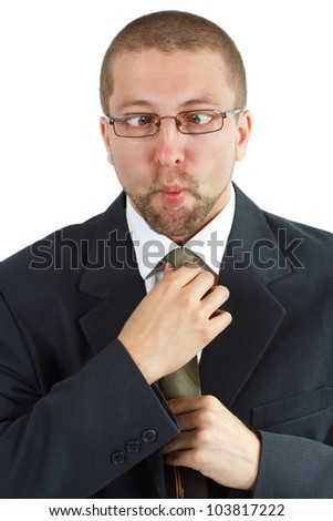 A young businessman with glasses, suit and tie, holding his tie, and making funny grimace squinting - isolated on white